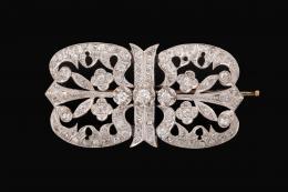 BROCHE ANTIGUO AÑOS 50, DE ORO BLANCO Y DIAMANTES Realizado en oro blanco de 18 kt., compuesto por motivos florales calados cuajados de diamantes tallas 8/8 y brillante antigua engastados en garras y grano, peso total aproximado: 3.28 ct. Falta una piedra