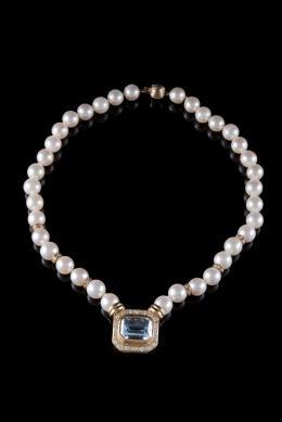 COLLAR De una vuelta de perlas australianas calibradas en 9 mm. con motivo central y entrepiezas realizados en oro con topacio azul talla rectangular y diamantes talla brillante, peso total aproximado: 1.10 ct. Cierre de oro gallonado.