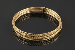 SEMANARIO Realizado en oro amarillo de 18k, formado por siete pulseras rígidas adiamantadas unidas entre si.