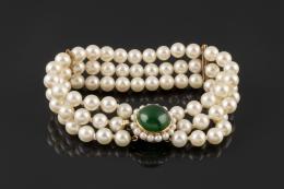 PULSERA Formada por tres hilos de perlas cultivadas calibradas de 6,5mm de diámetro, con broche realizado en oro amarillo de 18kt, formado por un cabujón de cristal verde orlado de perlitas.