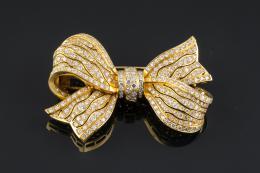 BROCHE Realizado en oro de 18 kt., en forma de lazo cuajado por diamantes talla brillante, peso total aproximado: 7.37 ct.