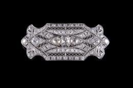 BROCHE ESTILO ART DECÓ DE ORO BLANCO Y DIAMANTES Realizado en oro blanco de 18 kt. con trabajo de filigrana y decoración geométrica de diamantes, talla antigua, formado por tres diamantes centrales, peso total aproximado: 1.70 ct. engastados en grano y cu