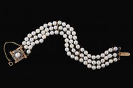 BRAZALETE DE PERLAS CULTIVADAS Y ORO ROSA Broche de oro rosa de 18 kt. formado por centro de perla cultivada y orla de piedras de color. Formado por tres hilos de perlas cultivadas calibradas en 5 mm de diámetro. Con cadena de seguridad.