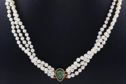 COLLAR DE TRES HILOS DE PERLAS, ORO Y ESMERALDAS De tres hilos de perlas cultivadas, calibradas en 5 mm. de diámetro aproximadamente, con tres abrazaderas de esmeralda y cierre en oro amarillo de 18 kt., con esmeralda talla pera cabujón engastada en garra