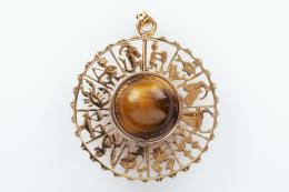 COLGANTE ZODIACAL DE ORO Y OJO DE TIGRE Realizado en oro amarillo de 18 kt., con la representación de lo signos del zodíaco rodeando una cuenta de ojo de tigre, calibrada en 14 mm. de diámetro.