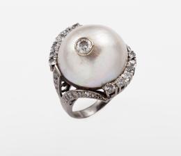 SORTIJA DE ORO BLANCO CON GRAN PERLA MABÉ Y DIAMANTES Realizada en oro blanco de 18 kt., con gran perla mabé central sobre bella galería calada, calibrada en 20 mm. de diámetro, con chatón incrustado que alberga un diamante talla brillante de 0.40 ct. Orl