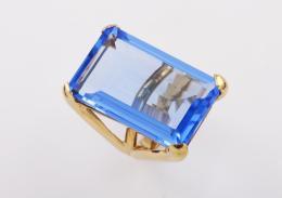 SORTIJA CONTEMPORÁNEA CON PIEDRA DE COLOR AZUL Y ORO AMARILLO Realizada en oro amarillo de 18 kt. Formada por una piedra central de color azul de 20 mm. x 32 mm., engastada en garras. Con hombros abiertos.